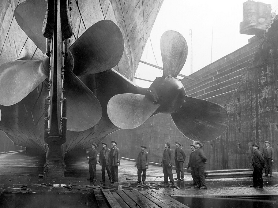 Closeup - Tiny humans stand underneath huge Titanic propellers - 100 year old photos