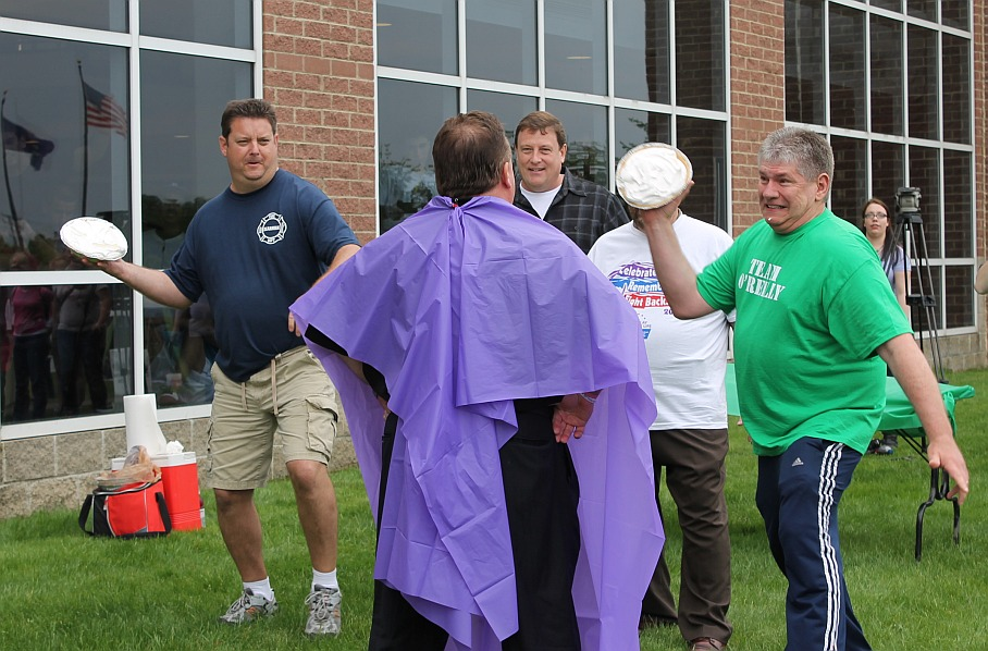 "Wayne County Commissioner Gary Woronchak winds up to hit Superintendent Brian Whiston with a pie during the ""Four Pies and a Poncho"" fund-raising event at the Relay for Life on Saturday. Whiston was supposed to be hit with four pies but, seen at left, Dearborn Firefighter Burn Drive Chairman Steve Worden was preparing to launch an all-out piefight among the participants."
